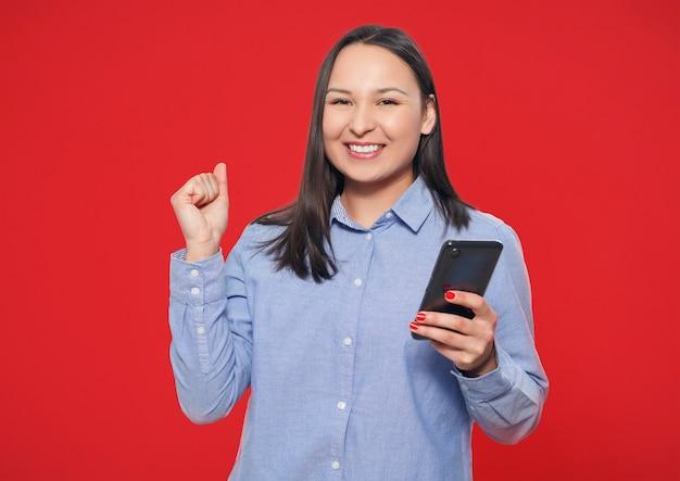 Mujer joven feliz con un teléfono inteligente en la mano sobre un fondo rojo.