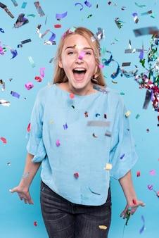 Mujer joven feliz en tiempo de confeti