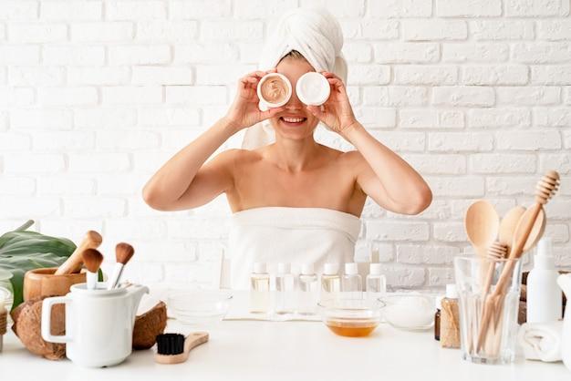 Mujer joven feliz en toallas de baño blancas divirtiéndose mientras hace procedimientos de spa