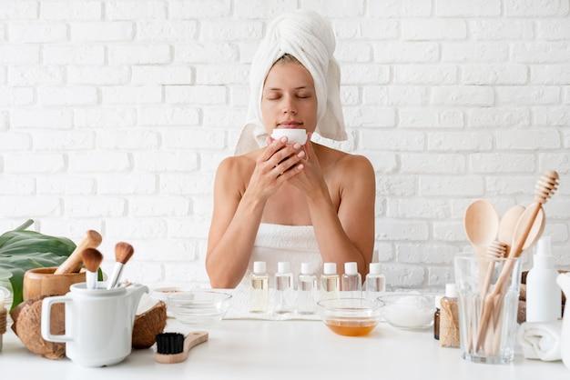 Mujer joven feliz en toallas de baño blancas que huele la crema haciendo procedimientos de spa
