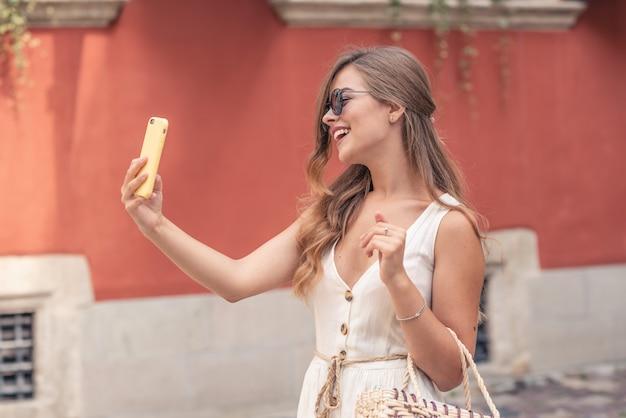 Mujer joven feliz tomando selfie. mujer tomando foto selfie con un smarphone en la ciudad