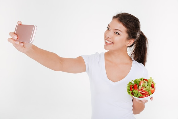 Mujer joven feliz tomar un selfie con ensalada de verduras