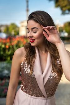 Mujer joven feliz en traje de noche caminando por la ciudad