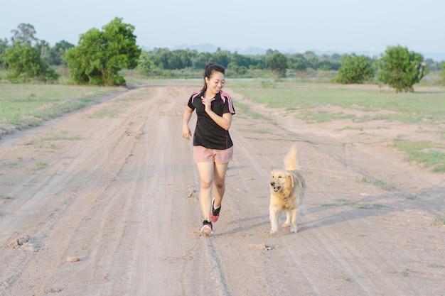 Mujer joven feliz trotar con su perro beagle