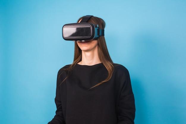 Mujer joven feliz usando un casco de realidad virtual en azul