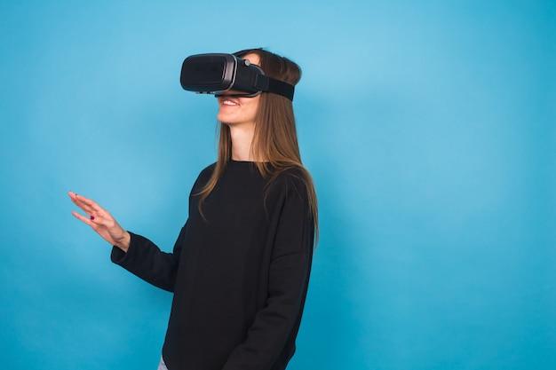 Mujer joven feliz usando un casco de realidad virtual.