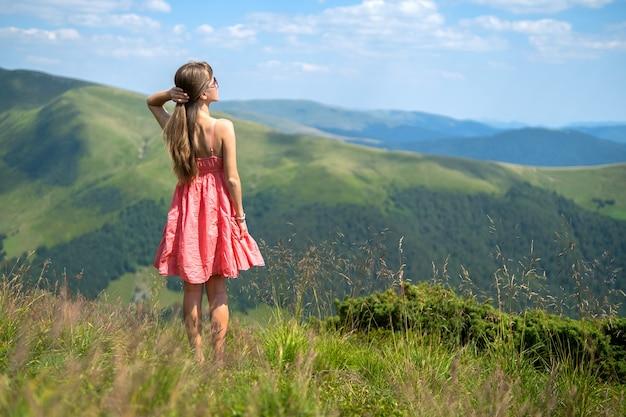 Mujer joven feliz en vestido rojo caminando sobre la pradera de la ladera en un día ventoso en las montañas de verano