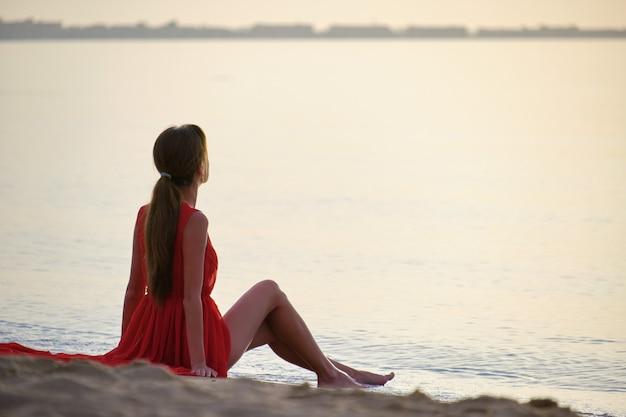 Mujer joven feliz en vestido rojo relajante en la playa de arena junto al mar disfrutando de la cálida mañana tropical.