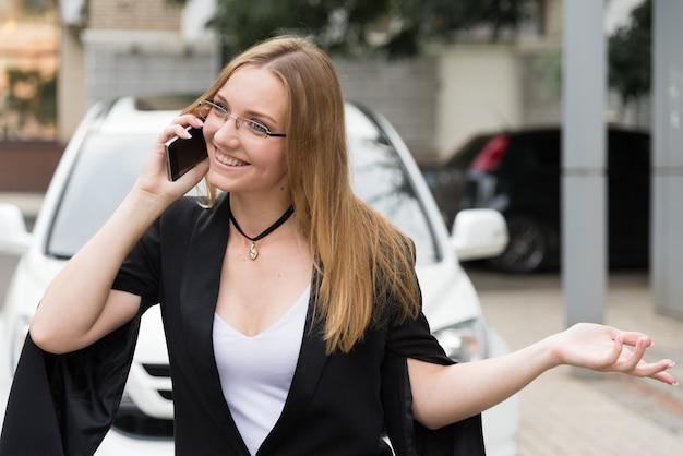 Mujer joven feliz en vidrios que habla en el teléfono cerca de un coche blanco.