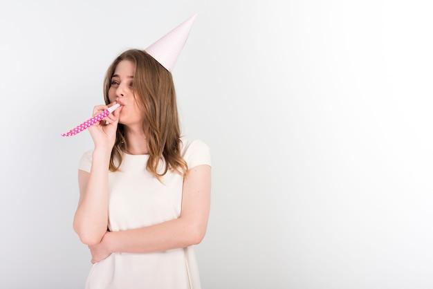 Mujer joven festiva en el sombrero de fiesta soplando ruido