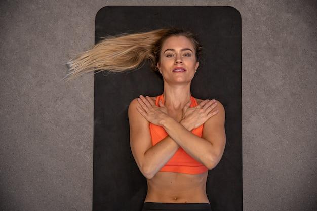 Una mujer joven con una figura deportiva practicando en el gimnasio, fitness y culturismo
