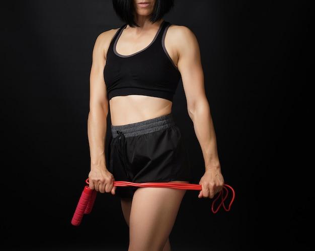 Mujer joven con una figura deportiva en uniforme negro tiene una cuerda roja para saltar