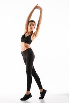 Mujer joven fitness calentamiento y mirando a otro lado