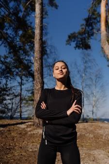 Mujer joven fitness camina en el parque y posando