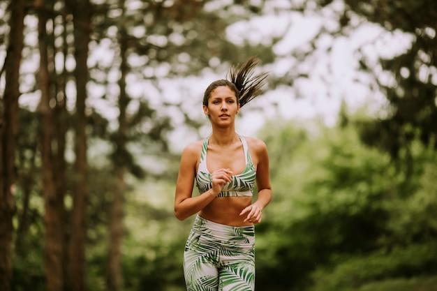 Mujer joven fitness correr en pista forestal