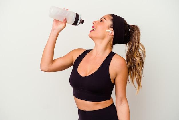 Mujer joven fitness deportivo bebiendo agua de botella aislado sobre fondo blanco.