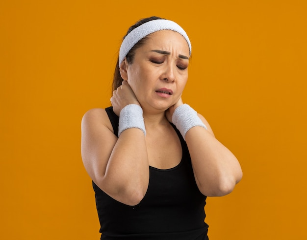 Mujer joven fitness con diadema y brazaletes con aspecto de malestar tocando su cuello sintiendo dolor de pie sobre la pared naranja