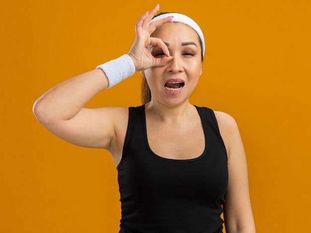 Mujer joven fitness con diadema y brazaletes haciendo bien firmar mirando a través de los dedos sonriendo