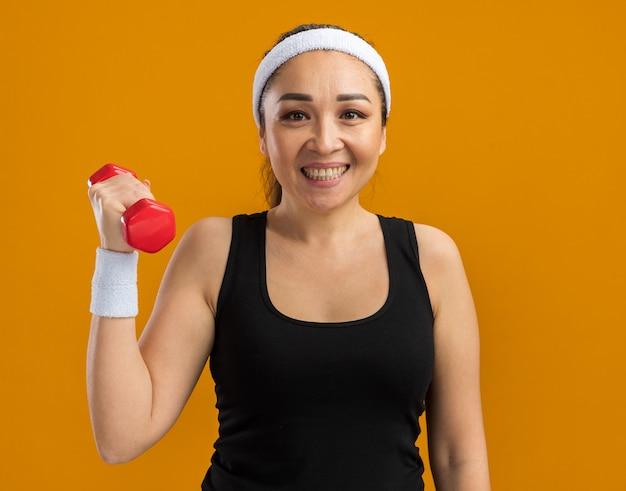 Mujer joven fitness con diadema y brazaletes levantando el brazo con mancuernas sonriendo alegremente
