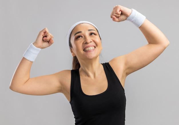 Mujer joven fitness con diadema y brazaletes levantando puños feliz y emocionado