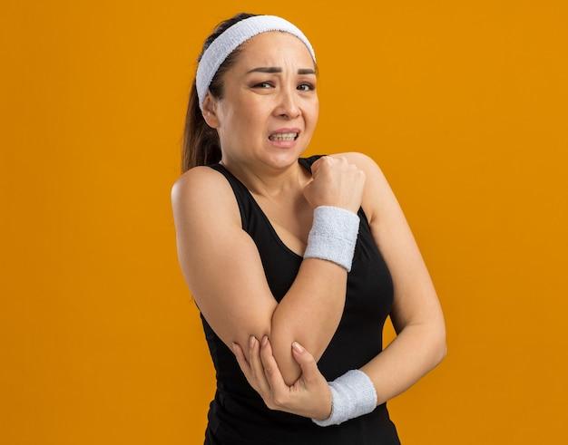 Mujer joven fitness con diadema y brazaletes mirando mal tocando su codo sintiendo dolor