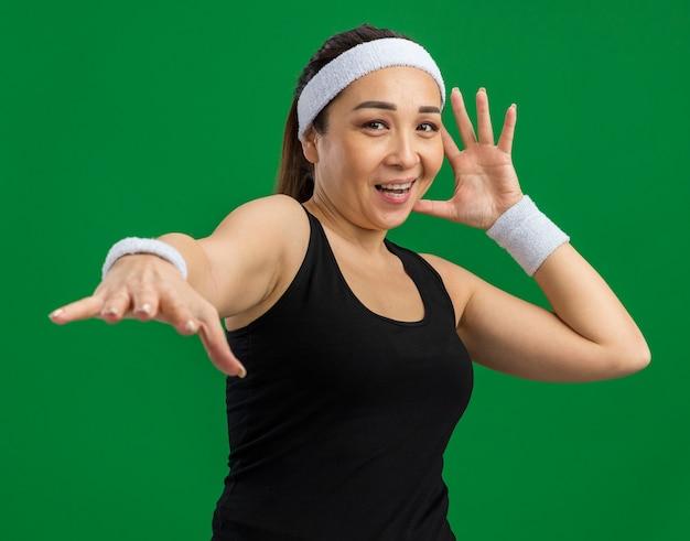 Mujer joven fitness con diadema y brazaletes sonriendo alegremente con el brazo extendido de pie sobre la pared verde