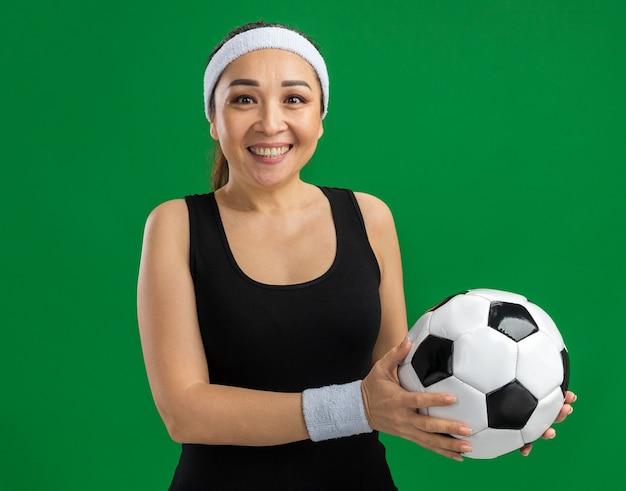 Mujer joven fitness con diadema y brazaletes sosteniendo un balón de fútbol sonriendo feliz y positivo