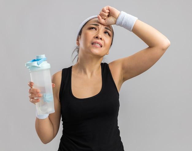 Mujer joven fitness con diadema y brazaletes sosteniendo una botella de agua que parece confundida con la mano en la cabeza por error de pie sobre la pared blanca