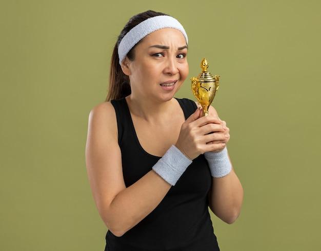 Mujer joven fitness con diadema y brazaletes sosteniendo trofeo con expresión escéptica