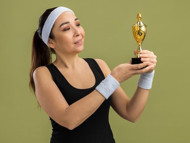 Mujer joven fitness con diadema y brazaletes sosteniendo trofeo mirándolo feliz y complacido