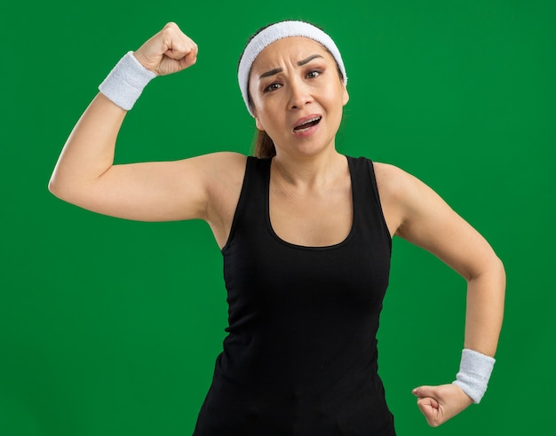 Mujer joven fitness con diadema y brazaletes tensos y seguros levantando puños mostrando fuerza y poder de pie sobre la pared verde