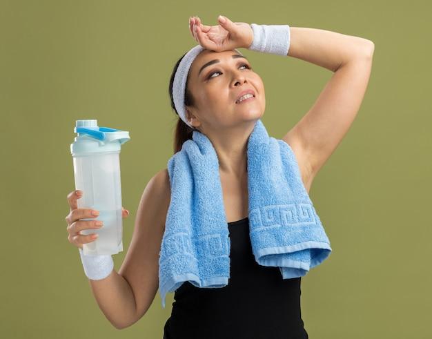 Mujer joven fitness con diadema y brazaletes con toalla alrededor del cuello sosteniendo una botella de agua mirando hacia arriba cansado y con exceso de trabajo