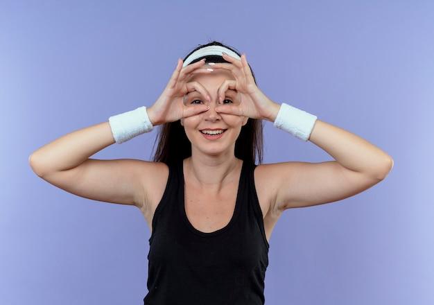 Mujer joven fitness en diadema haciendo gesto binocular con los dedos mirando a la cámara a través de los dedos sonriendo de pie sobre fondo azul.