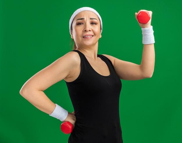 Mujer joven fitness con diadema con pesas haciendo ejercicios tensos y seguros de pie sobre la pared verde