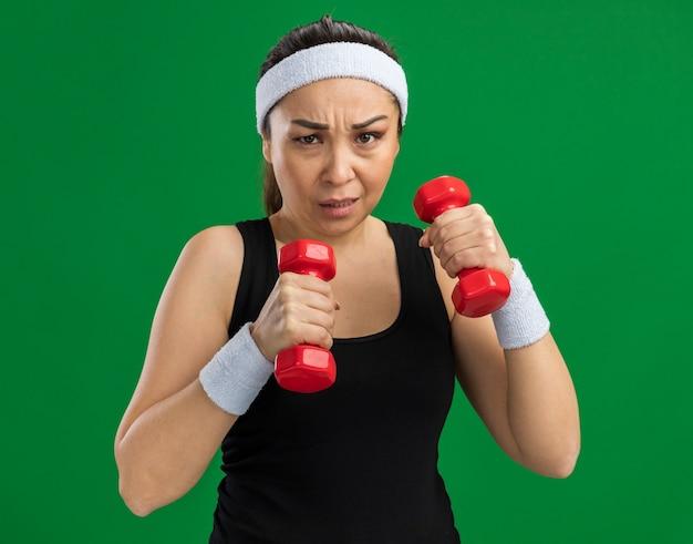 Mujer joven fitness con diadema con pesas haciendo ejercicios tensos y seguros