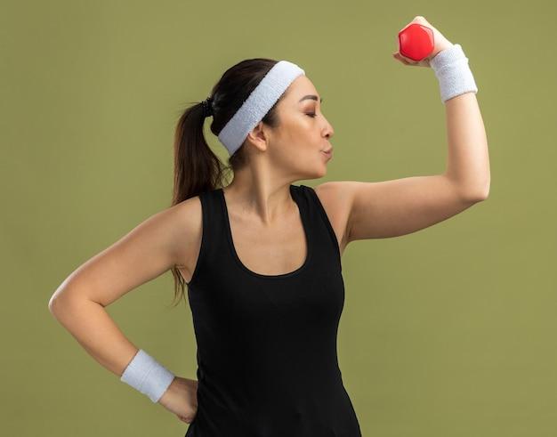 Mujer joven fitness con diadema sosteniendo mancuernas levantando puño va a besar sus bíceps