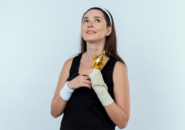 Mujer joven fitness en diadema sosteniendo su trofeo mirando hacia arriba sintiéndose agradecido de pie sobre fondo blanco.