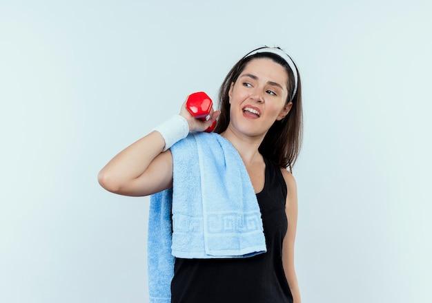 Mujer joven fitness en diadema con una toalla sobre su hombro trabajando con mancuernas mirando confiado de pie sobre la pared blanca