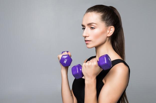 Mujer joven fitness ejercicio con pesas aislado en la pared blanca