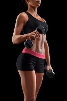 Mujer joven fitness en entrenamiento bombeo de los músculos con mancuernas