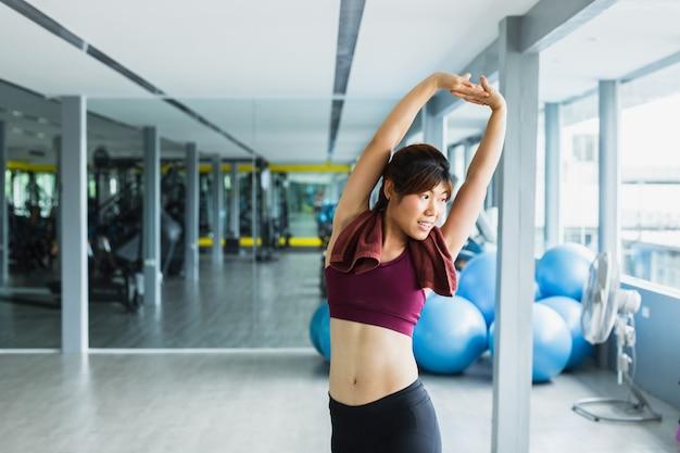 Mujer joven fitness estirando los brazos para calentar.