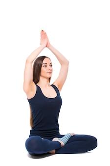 Mujer joven fitness haciendo yoga sobre fondo blanco.