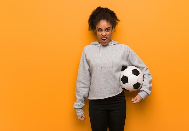Mujer joven fitness negro gritando muy enojado y agresivo.