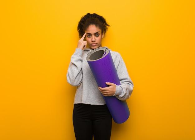 Mujer joven fitness negro haciendo un gesto de concentración. sosteniendo una estera.