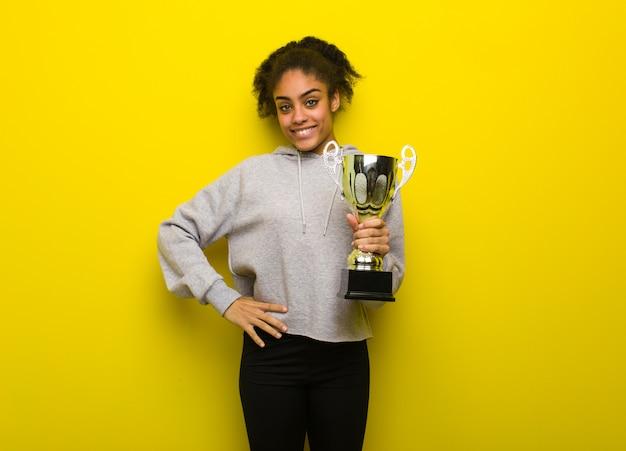 Mujer joven fitness negro con las manos en las caderas. sosteniendo un trofeo.