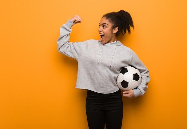 Mujer joven fitness negro que no se rinde. sosteniendo un balón de fútbol.
