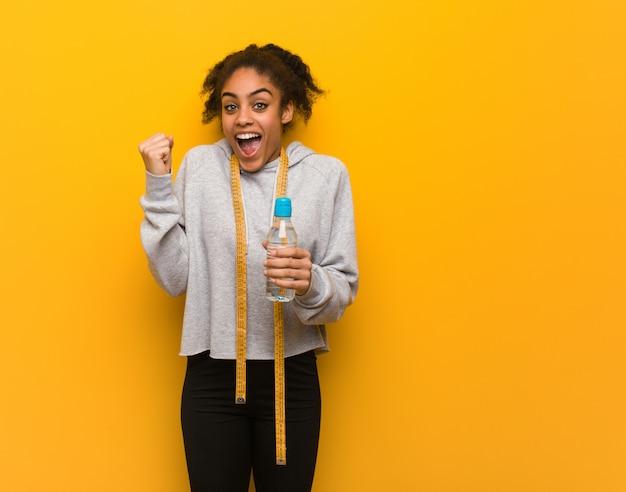 Mujer joven fitness negro sorprendido y conmocionado. sosteniendo una botella de agua.