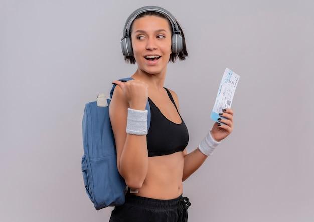 Mujer joven fitness en ropa deportiva con auriculares en la cabeza con mochila sosteniendo boleto aéreo mirando a un lado apuntando hacia atrás con el pulgar parado sobre la pared blanca
