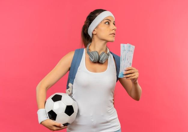 Mujer joven fitness en ropa deportiva con diadema y auriculares alrededor de su cuello sosteniendo boletos de avión y balón de fútbol mirando a un lado con cara seria de pie sobre una pared rosa