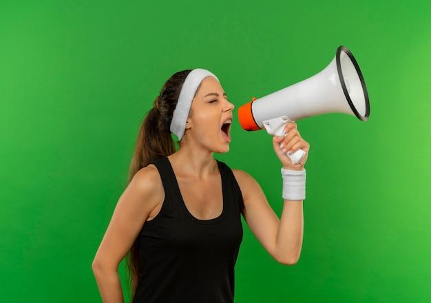 Mujer joven fitness en ropa deportiva con diadema gritando a megáfono parado sobre pared verde